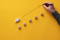 Male hand drawing an arrow pointing upwards in front of an origami made paper boat. Over yellow background.