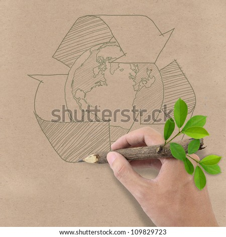 Male hand drawing recycle and earth symbol on Brown Recycled Paper.