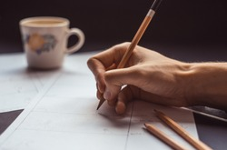 male hand drawing storyboard conceptual ideas with coffee cup in the background, hard work sketching art concept