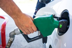 Male hand filling gasoline to the car.