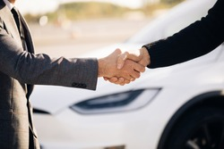 Male hand gives a car keys to male hand in the car dealership close up. Unrecognized auto seller and a man who bought a vehicle shake hands. Dealer giving key to new owner in auto show or salon.