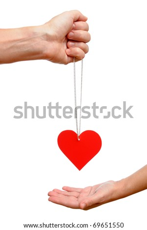 Male hand gives into female hand red heart on chain