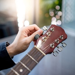 Male hand guitarist adjusting pegs on acoustic guitar during music lesson at home. String musical instrument concept