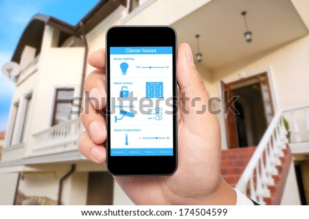 male hand hold a phone with system clever house on a screen on the background of the house #174504599