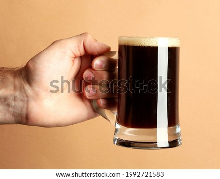Male hand hold glass of beer on brown background Stockfoto ©