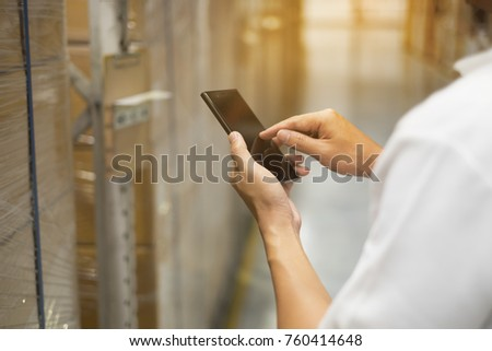 male hand hold smartphone to check product in warehouse for import and export the shipping cargo. image with lighting flare effect