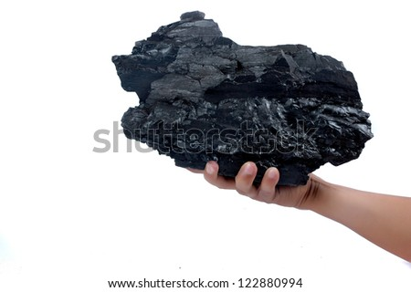 male hand holding a big lump of coal isolated on white background