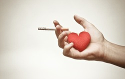 male hand holding a cigarette with a red heart / making to right decision about smoking concept