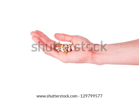 Male hand holding a handful of medical pills isolated on white.