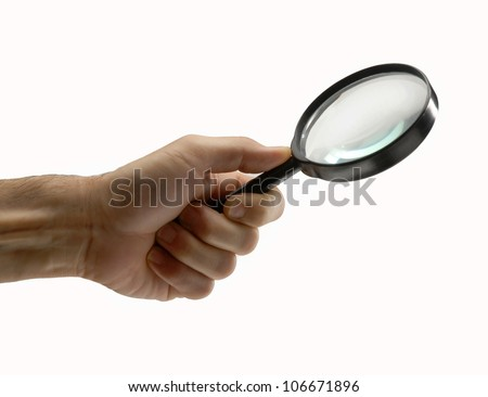 Male hand holding a magnifying glass on white background.