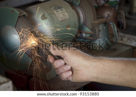 Male hand holding a metal rod on the bench grinder amongst sparks