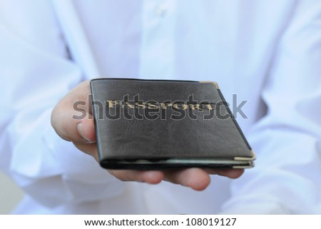 male hand holding a passport