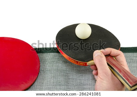 Male hand holding a ping pong racket and a table tennis ball above a net, isolated on white