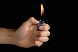 male hand holding a purple lighter with a large flame on a black background
