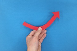 Male hand holding a red arrow graph going upward in blue background. Business recovery, growth, bounce back concept.