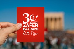 Male hand holding a red paper with greeting message in Turkish. Happy August 30, Victory Day in English. August 30, Zafer Bayrami is the victory day of Turkey.