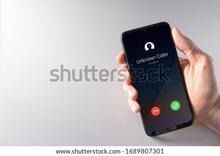 Male hand holding a smartphone with unknown caller displayed on screen. Privacy, fraud, cybercrime and spying concepts Сток-фото ©