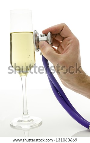 Male hand holding a stethoscope on a glass of wine.Concept of consequences of drinking alcohol.