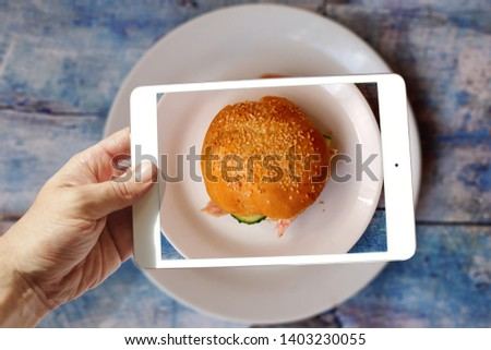 male hand holding a tablet taking a picture of a chicken burger on a plate