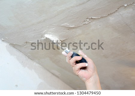 male hand holding a trowel on weight closing up cracks in the ceiling #1304479450