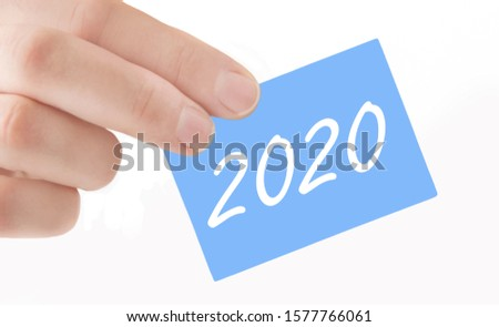 Male hand holding blue label 2020