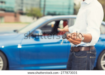 Male hand holding car keys offering new blue car on background #277873031