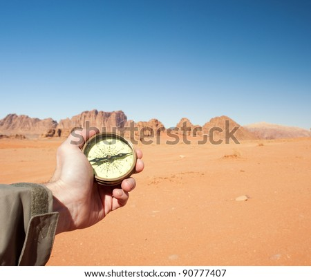 male hand holding compass in the desert