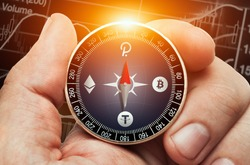 Male hand holding compass with bitcoin, ethereum, polkadot and tether logo in front of stock market chart data. Compass needle showing  polcadot coin symbol.