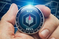 Male hand holding compass with chainlink altcoin in front of stock market chart data. Compass needle showing buy word. Cryptocurrency trading concept.