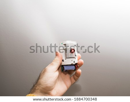 Photo of  Male hand holding futuristic safety home laser beamer security alarm device with red laser light in operation to detect intruders and thefts - isoalted on white