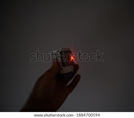 Photo of  Male hand holding futuristic safety home laser beamer security alarm device with red laser light in operation to detect intruders and thefts - gray modern background