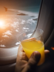 male hand holding glass of orange juice near the window of airplane. man looking through the windows of airplane and drinking juice during flight. Selective focus on juice