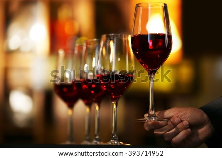 Male hand holding glasses of wine in the bar #393714952