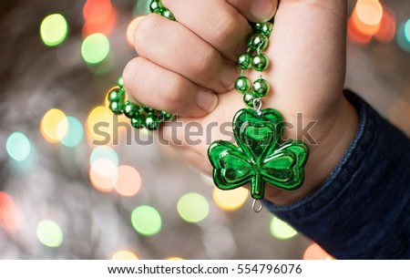 Male hand holding green clover necklace. St Patricks day preparation