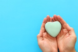 male hand holding heart over blue background. copy space, top view