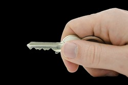 Male hand holding house key. Isolated over black background.