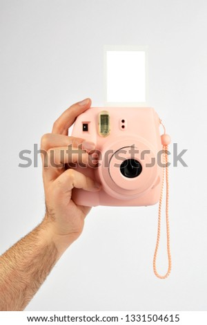 Male hand holding instant camera