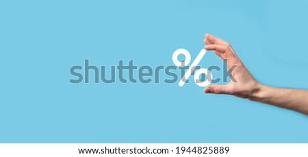 Male hand holding interest rate percent icon on blue background. Interest rate financial and mortgage rates concept.Banner with copy space.