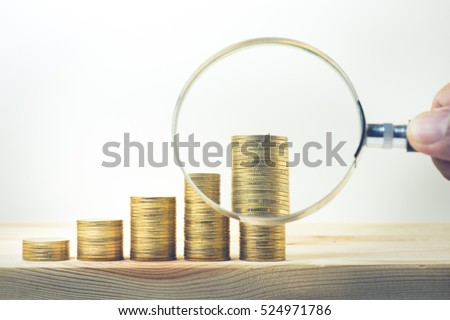 Male hand holding magnifying glass with coin stacked on wood table.For business growth and financial concept