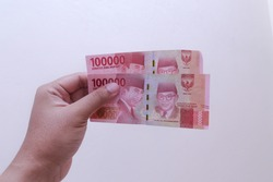Male hand holding one hundred thousand rupiah bank notes over the gray copyspace background. Indonesian currency.