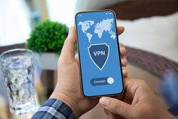 male hand holding phone with app vpn on screen over table with in cafe