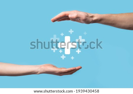 Male hand holding plus icon on blue background. Plus sign virtual means to offer positive thing (like benefits, personal development, social network)Profit,health insurance, growth concepts. Foto stock ©