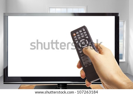 Male hand holding remote control and the TV in a modern room