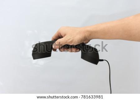 male hand holding retro telephone on white background. #781633981