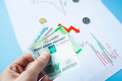 Male hand holding rouble bills on exchange rate of russian ruble and red arrow. ruble depreciation. Exchange rate of rouble fall. Rouble to dollar