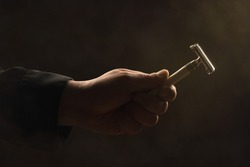 male hand holding safety razor before a dark Background
