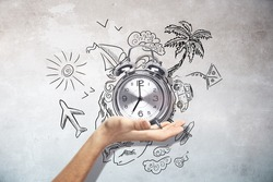 Male hand holding silver alarm clock on concrete wall background with travel sketch. Traveling time concept