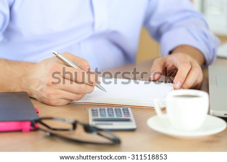Male hand holding silver pen ready to make note in opened notebook. Businessman or employee at workplace writing business ideas, plans or tasks at personal organizer. Office life or education concept