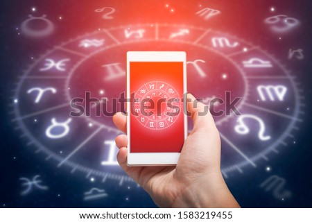 Male hand holding smart phone device with astrology app, close up. Astrology and horoscope reading concept.