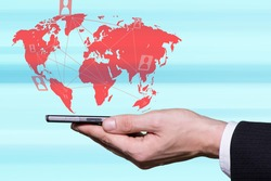 Male hand holding smartphone and world map in background